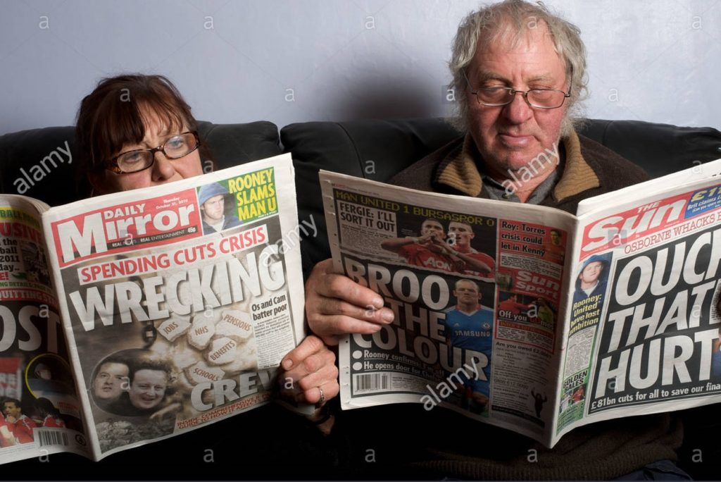 Two old people reading tabloids